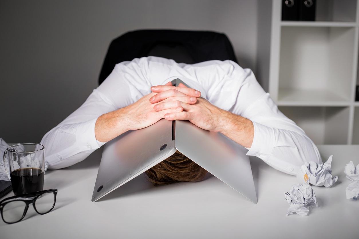 Man hiding under laptop